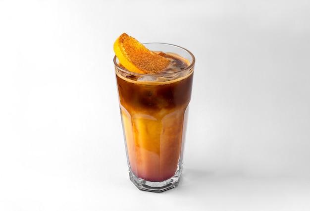 Przezroczysta szklanka żółtego orzeźwiającego letniego napoju z plasterkami pomarańczy, kostkami lodu i syropem czekoladowym na białym i szarym tle z naturalnym cieniem i przestrzenią do kopiowania