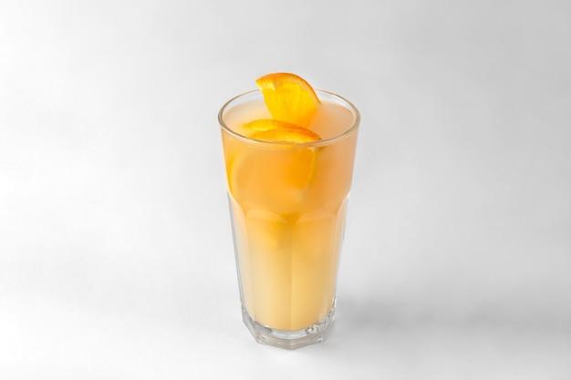 Przezroczysta szklanka żółtego orzeźwiającego letniego napoju z plasterkami pomarańczy na białym i szarym tle z naturalnym cieniem i przestrzenią do kopiowania