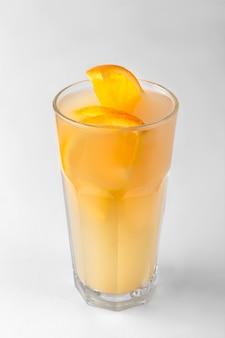 Przezroczysta szklanka żółtego orzeźwiającego letniego napoju z plastrami pomarańczy na biało-szarej powierzchni z naturalnym cieniem, pionowe zdjęcie