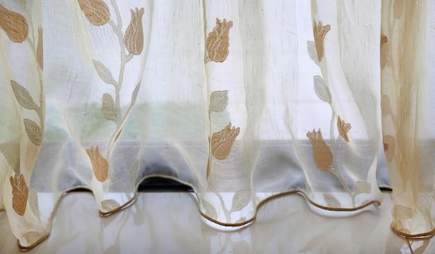 Przezroczysta tkanina zasłonowa z motywem kwiatowym.