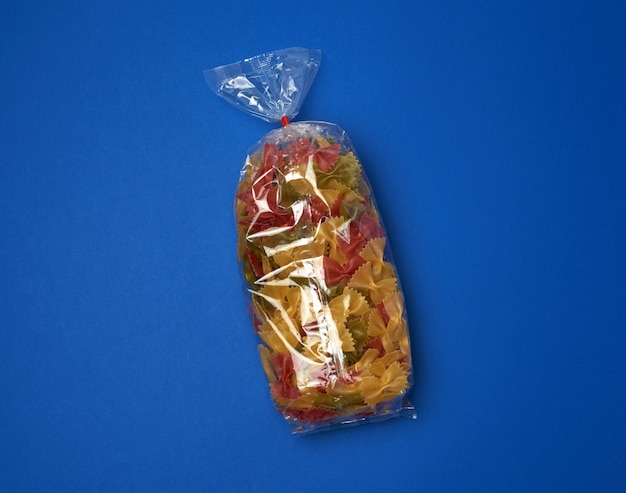 Przezroczysta torebka celofanowa z surowym kolorowym makaronem w formie kokardek