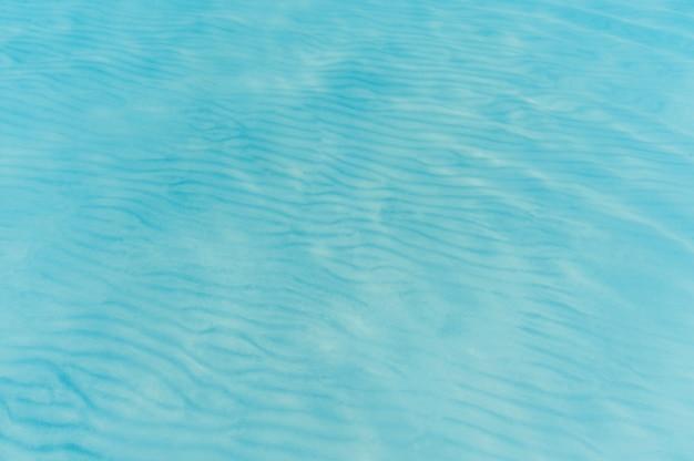 Przezroczysta woda morska i dno piasku