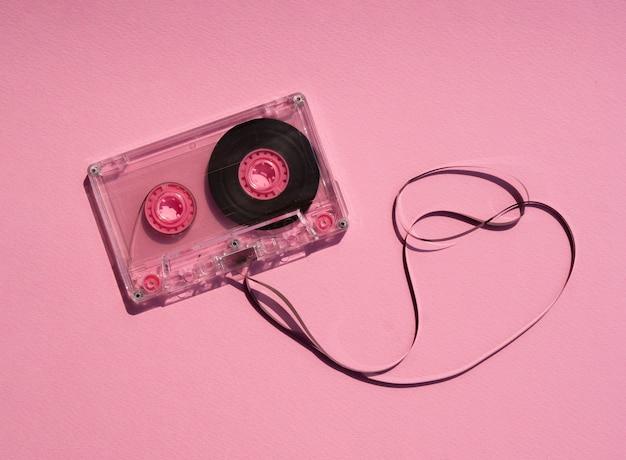 Przezroczysta zepsuta kaseta magnetofonowa na różowym tle