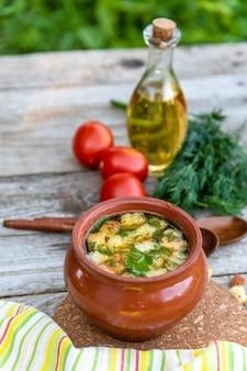Przezroczysta zupa w glinianym garnku z grzankami i koperkiem w stylu wegetariańskim, butelka z oliwą i pomidorami.