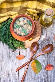Przezroczysta zupa w glinianym garnku z krakersami i koperkiem wegetariańska. widok z góry.