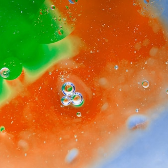 Przezroczyste bąbelki na zielono i pomalowane na pomarańczowo tło