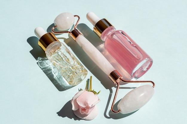 Przezroczyste flakony z serum kosmetycznym, kwasem hialuronowym, 24-karatowym złotem i wodą różaną na niebieskim tle z masującym wałkiem kwarcowym. koncepcja leczenia luksusowego domu do pielęgnacji twarzy i ciała.