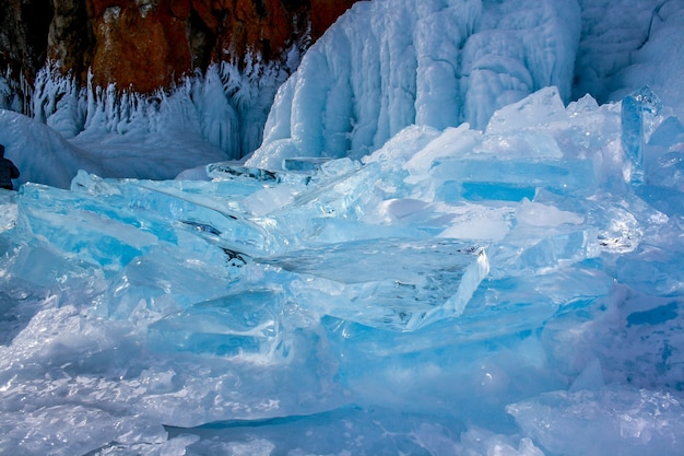 Przezroczyste kawałki lodu w pobliżu klifu nad jeziorem bajkał. piękny niebieski kolor lodu. na skale jest czerwony mech.
