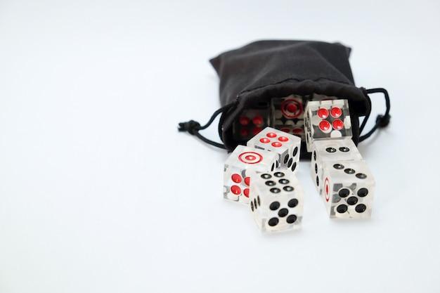 Przezroczyste kostki z czarnej torby na białym tle