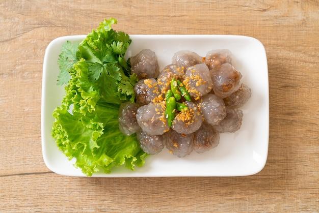 Przezroczyste kulki nazywają się saku sai moo lub gotowane na parze knedle z tapioki z nadzieniem wieprzowym