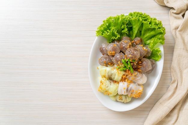 Przezroczyste kulki nazywają się saku sai moo lub kulka z pierożkami z tapioki na parze z nadzieniem wieprzowym i ryżem wieprzowym na parze