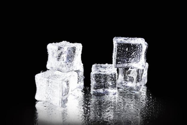 Przezroczyste mokre kostki lodu z kropelkami wody na czarnej lustrzanej powierzchni.
