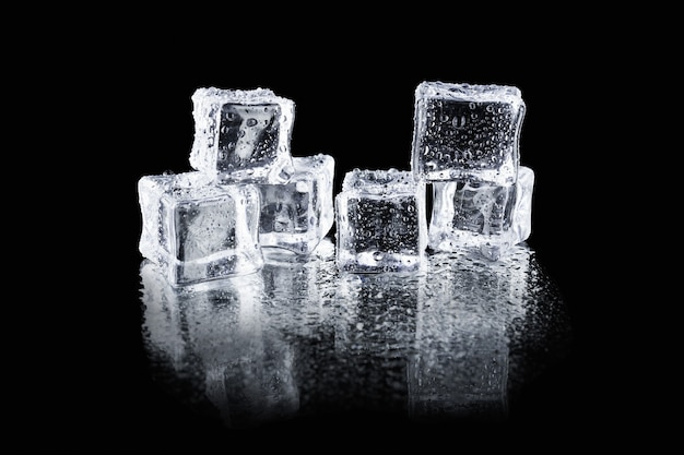 Przezroczyste mokre kostki lodu z kropelkami wody na czarnej, odbijającej światło powierzchni.