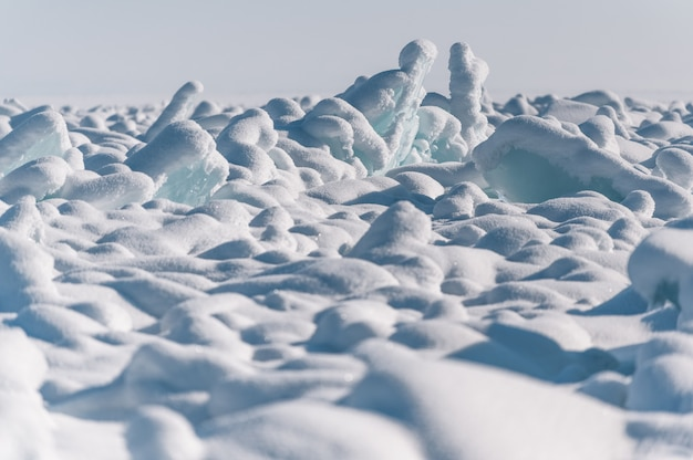 Przezroczyste niebieskie kry ułożone w stosy lodu na tle błękitnego nieba w słoneczny dzień
