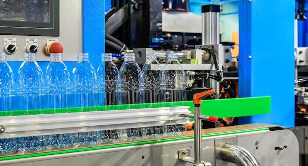 Przezroczyste plastikowe butelki przenoszone na zautomatyzowane systemy przenośników automatyzacja przemysłowa dla opakowań
