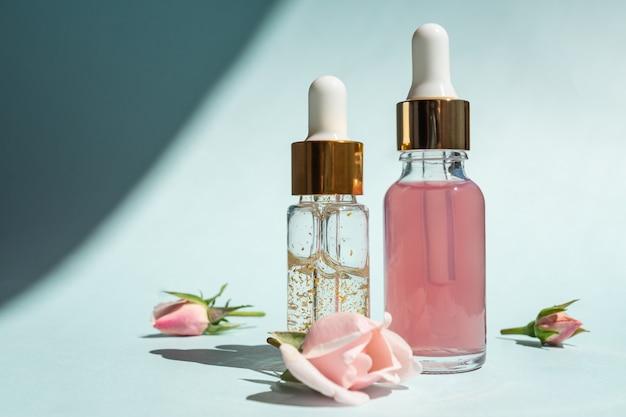 Przezroczyste szklane butelki kosmetyczne z zakraplaczem na niebieskim tle. koncepcja kosmetyków naturalnych, naturalny olejek różany i produkty do pielęgnacji skóry