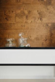 Przezroczyste szklane karafki na półce na drewnianym tle