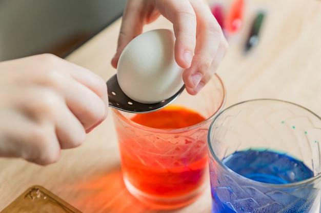 Przezroczyste szklane kubki z kolorową wodą. dziecko wkłada łyżkę do białego jajka.