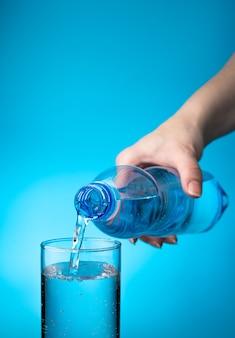 Przezroczyste szkło wypełnione jest wodą z plastikowej butelki na jasnoniebieskim tle.