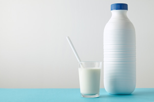 Przezroczyste szkło ze świeżym mlekiem i białą słomką do picia w pobliżu pustej, ryflowanej plastikowej butelki z niebieską nakrętką