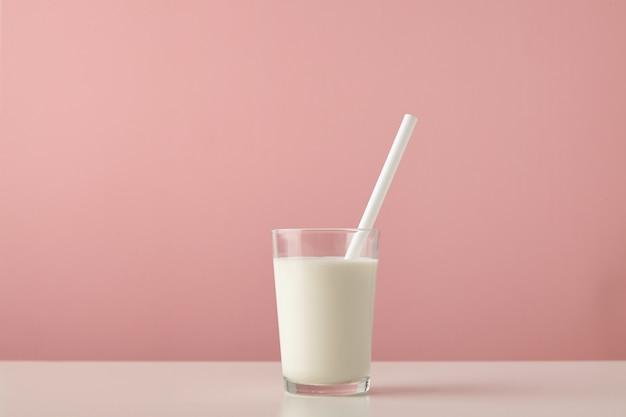 Przezroczyste szkło ze świeżym organicznym mlekiem i białą słomką wewnątrz na białym tle na pastelowym różowym tle na drewnianym stole