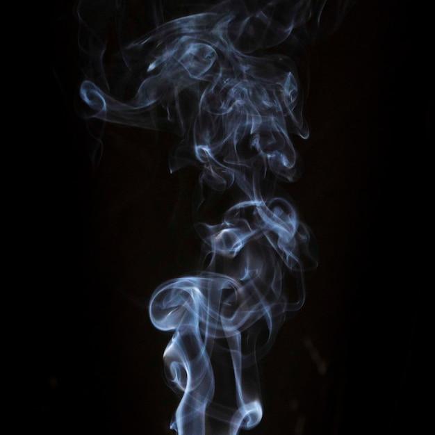 Przezroczysty biały wir dymu na czarnym tle ciemności