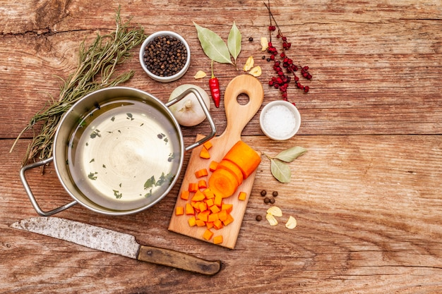 Przezroczysty bulion z kaczki na patelni ze świeżymi składnikami. tradycyjny bulion dla zdrowych potraw. przyprawy, warzywa, stary drewniany stół