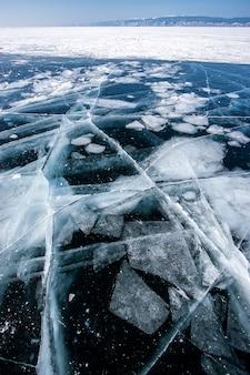 Przezroczysty ciemny lód na jeziorze bajkał z zamrożonymi kawałkami lodu i dużymi pięknymi pęknięciami