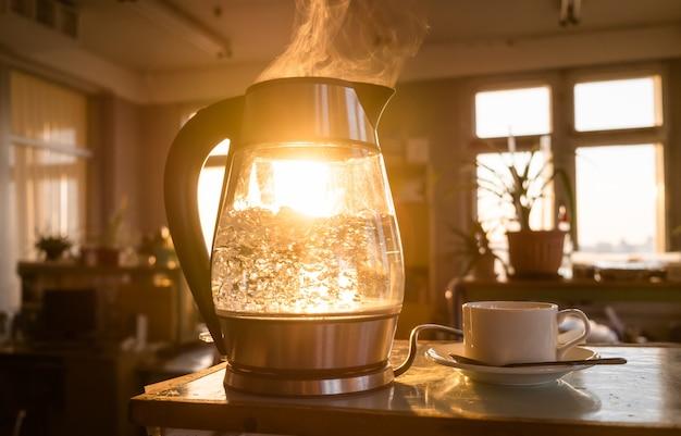 Przeźroczysty czajnik wody gotuje się na tle zachodzącego słońca przeświecającego przez okno