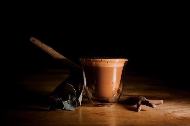 Przezroczysty kubek wypełniony gorącym i aromatycznym napojem kawowym z mlekiem