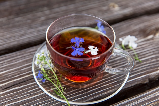 Przezroczysty kubek z herbatą z ziołami i małymi kwiatami. oczyszczanie zdrowia i detoksykacji.