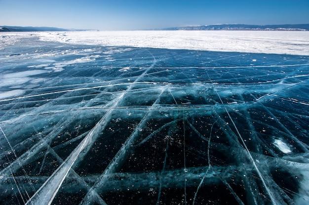 Przezroczysty lód na jeziorze bajkał z dużymi pięknymi pęknięciami w słoneczny dzień
