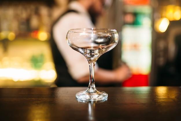 Przezroczysty napój w szkle na ladzie barowej