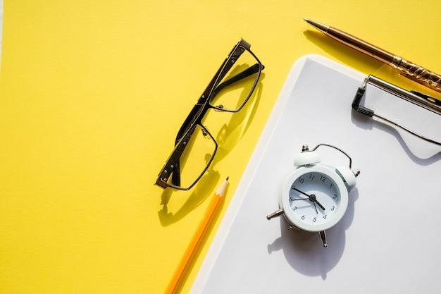 Przezroczysty notatnik, okulary, długopis i mały zegar na żółtym stole. materiały biurowe i okulary. prezentacja makiety. zarządzanie czasem.