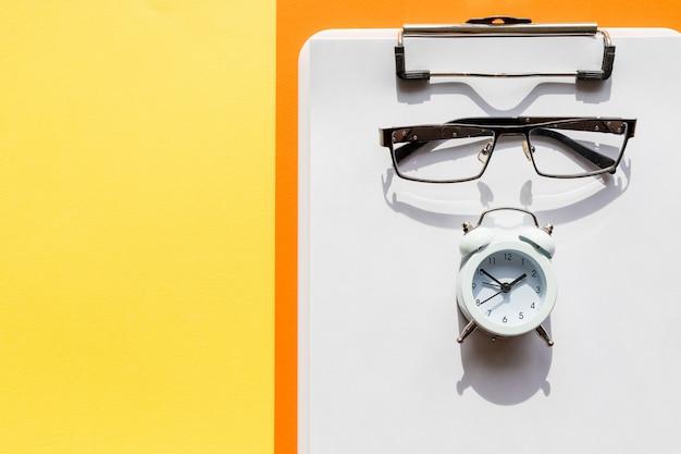 Przezroczysty notatnik, okulary, długopis i mały zegar na żółtym stole, płasko ułożony. materiały biurowe i okulary. prezentacja makiety. zarządzanie czasem.