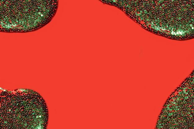 Przezroczysty płyn z zielonym brokatem wylewającym się na koralowo-czerwone tło świąteczne dla twojego projektu