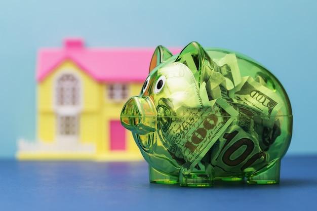 Przezroczysty skarbonka pełna dolarów i domek z zabawkami na kolorowej koncepcji oszczędzania na dom
