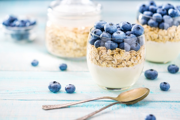 Przezroczysty słoik jogurtu z jagodami i płatkami owsianymi