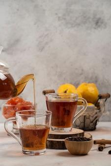 Przezroczysty szklany czajniczek nalewa herbatę w szklanym kubku na marmurowym stole.