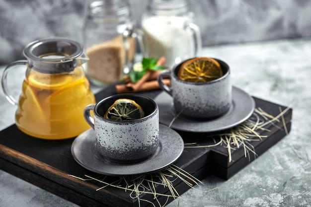 Przezroczysty szklany czajniczek z herbatą cytrusową i filiżankami, zestaw do herbaty na drewnianym stole. z bliska, szare, miękkie światło.