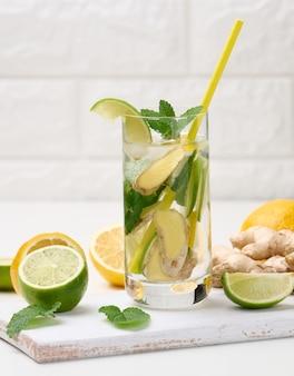 Przezroczysty szklany kubek z cytryną, kawałkami limonki i liśćmi mięty i kawałkami imbiru na białym stole, detoks.