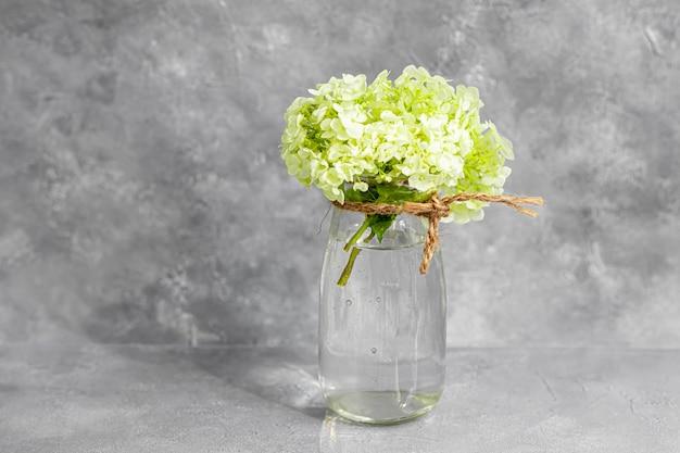 Przezroczysty wazon pełen świeżo ściętych kwiatów na szarym tle
