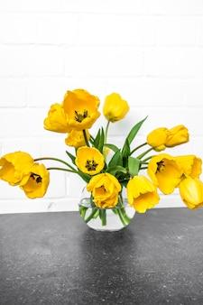 Przezroczysty wazon z żółtymi tulipanami