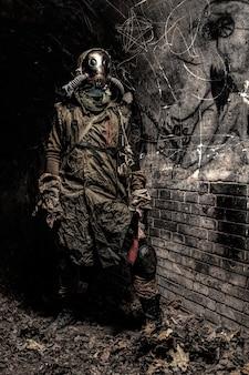 Przeżył katastrofę nuklearną lub globalną katastrofę ekologiczną człowiek ubrany w szmaty, maskę gazową lub aparat oddechowy i ukrywający się w ciemnym lochu, katakumbach lub podziemnym tunelu z ręcznie robioną maczetą