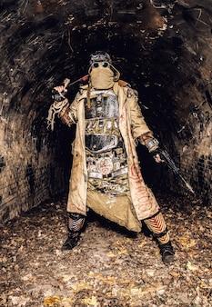 Przeżyła katastrofę nuklearną i mieszkała w katakumbach lub podziemnych tunelach miejskich istota ludzka, nosząca szmaty i ręcznie robioną kamizelkę kuloodporną, chowająca twarz za maską, uzbrojona w pistolet i maczetę