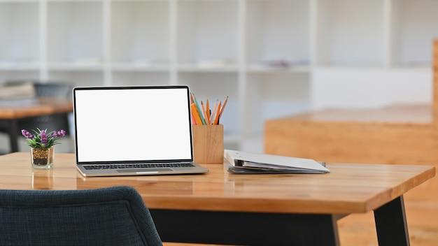 Przód białego pustego ekranu laptopa, uchwyt na ołówek, teczki na dokumenty, roślina doniczkowa na biurku.
