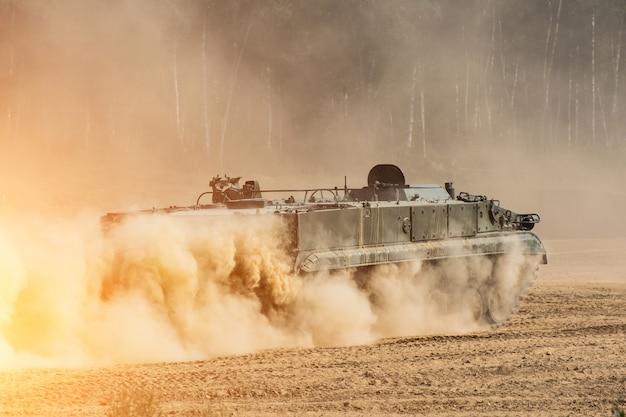 Przód czołgu, jadący przez kurz.