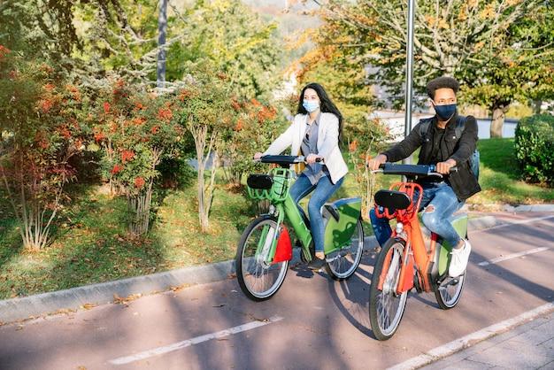 Przód dwóch młodych mężczyzn i kobiet jadących ścieżką rowerową ze wspólnym elektrycznym rowerem w pięknym parku z wieloma drzewami o zachodzie słońca w masce na twarz na pandemię koronawirusa 2020