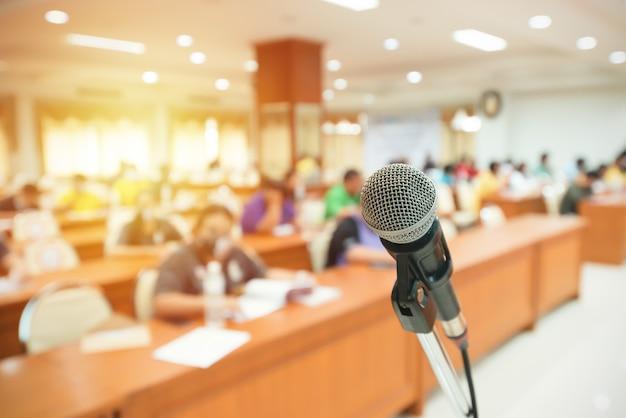 Przód mikrofonu z rozmytym tłem wielu ludzi na sali. mikrofon na scenie. koncepcja działalności wewnętrznej. koncepcja seminarium lub spotkania.