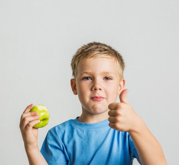 Przód młody chłopak z zielonym jabłkiem